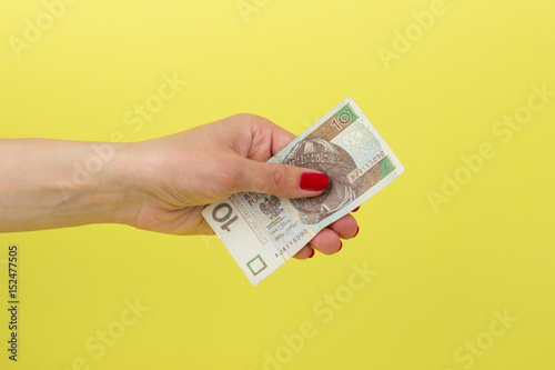 Pinturas sobre lienzo  Polish zloty in the woman's hand, yellow background