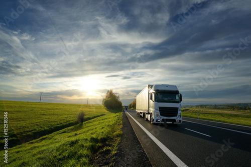 Zdjęcie XXL Biel ciężarówki jeżdżenie na asfaltowej drodze między polami i łąkami w wiejskim krajobrazie przy zmierzchem
