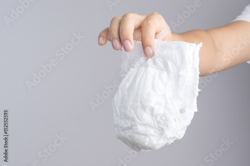 Fotografiet  Hand holding used baby diaper