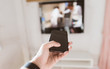 Closeup on hand holding smartphone and use a app with remote control and surfing programs on television in selective focus.