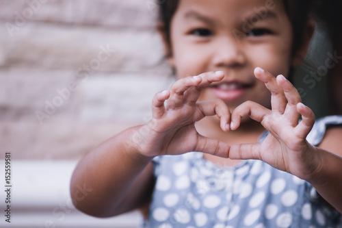 Slika na platnu Asian little girl making heart shape with hands in vintage color tone