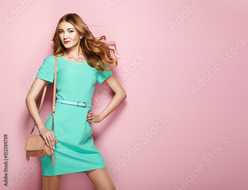 Blonde young woman in elegant green dress. Girl posing on a pink background. Jewelry and hairstyle. Girl with handbag. Fashion photo Wall mural