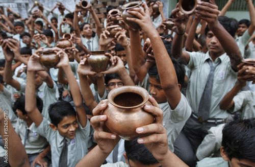 School children chant a mantra while holding a mixture of