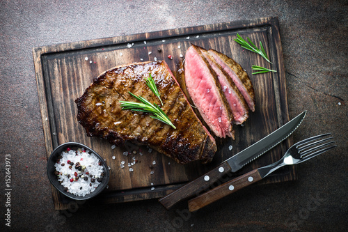 Aluminium Prints Steakhouse Grilled beef steak on wooden board. Top view.