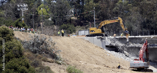 Workers operate on the Mulholland bridge during its partial
