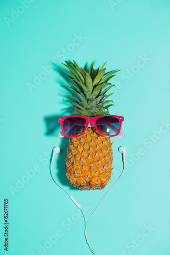 Papiers peints Magasin de musique Fashion pineapple with sunglasses and headphones listens to music over blue background