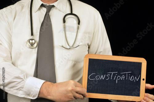 Valokuva  Médecin tenant une ardoise avec constipation écrit dessus