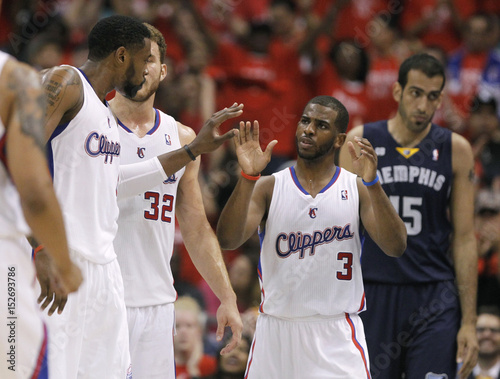 Clippers point guard Chris Paul slaps hands with teammates