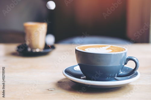 Two cups of hot coffee on wooden table in vintage cafe