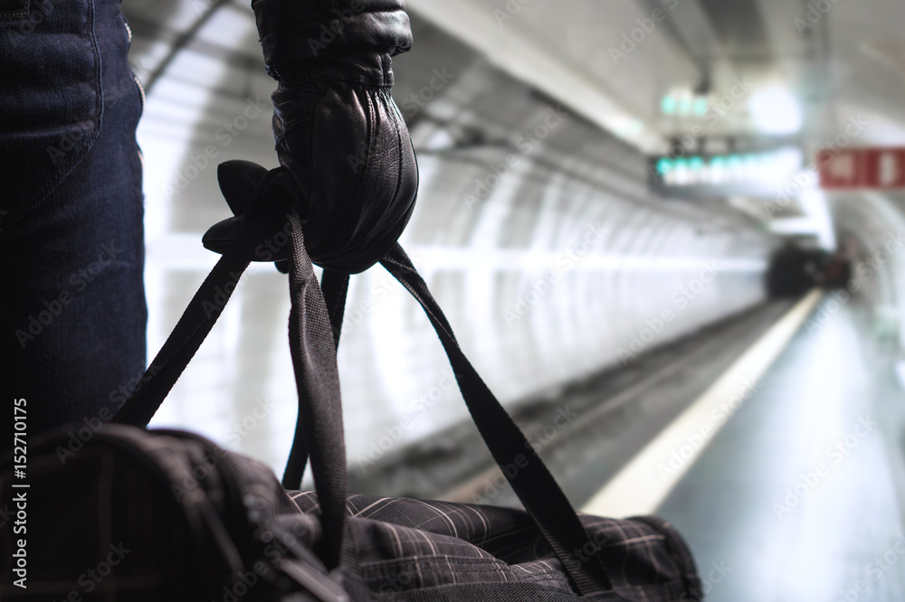 Fototapeta Terrorist in subway tunnel. Man planning bomb attack and strike in underground. Criminal standing in metro tunnel. Black bag and leather gloves. Security threat in public transportation concept.