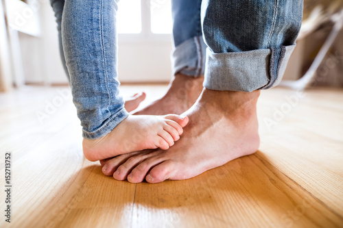 Obraz Beautiful young family. Bare feet of father and daughter. - fototapety do salonu