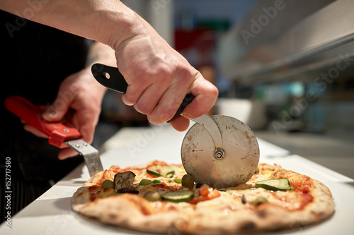 Foto op Plexiglas Pizzeria cook cutting pizza to pieces at pizzeria