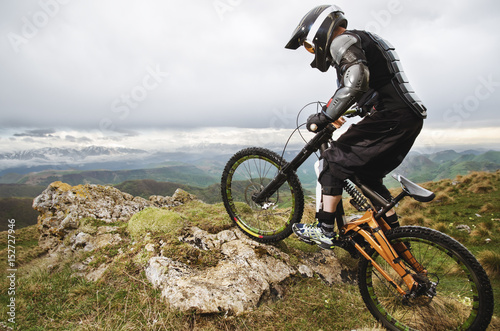Ryder in full protective equipment on the mtb bike climbs on a rock against the Canvas Print