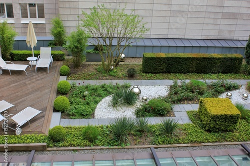 Poster Jardin Roof garden with green plants and silver which balls and wooden terrace with rest chairs