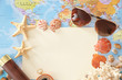 Travel concept. Composition with paper and sea shells on world map background