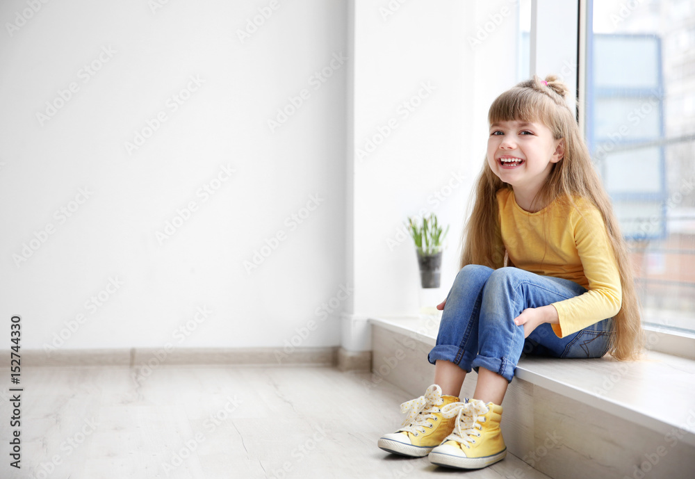 Fototapety, obrazy: Little fashion girl sitting on window sill in light room