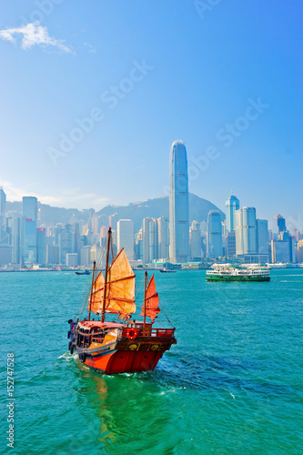 fototapeta na ścianę View of Hong Kong skyline with a red Chinese sailboat passing on the Victoria Harbor in a sunny day.