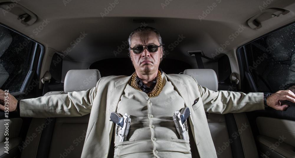 Fototapeta Man in a white suit with a gun, ganster, mafia in the car