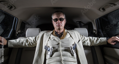 Photo  Man in a white suit with a gun, ganster, mafia in the car