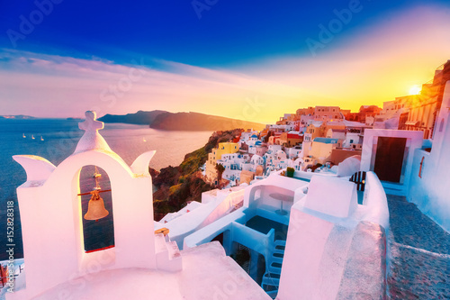 Poster Rose clair / pale Classical view at sunset over chapel in Oia (Ia) village on Santorini volcano island in Greece. Breathtaking epic sunset scenery. Popular travel tourist destination for romantic trip.