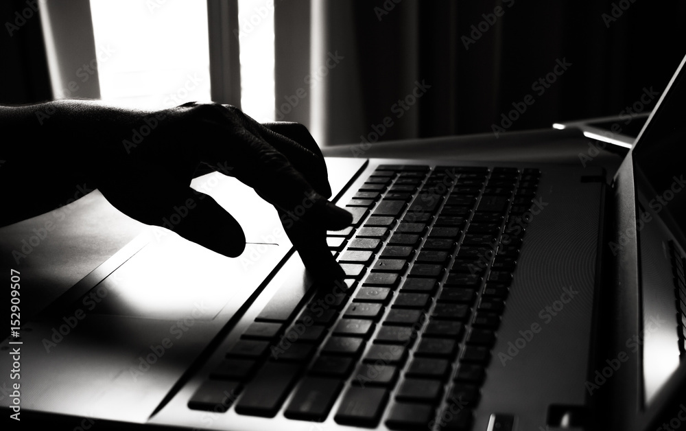 silhouette black and white of anonymous hacker typing on keyboard of laptop for remotely hacking and receiving