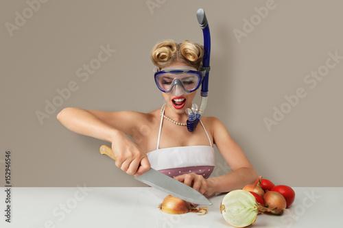 Fototapeta Young woman cutting onion in diving mask obraz