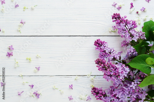 Photo sur Toile Lilac Pattern of a branch of lilac and other spring flowers on a white wooden background. top view. flat lay. Holiday concept. Copy space