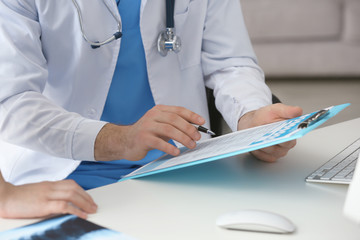 Hands of doctor with clipboard and pen working in clinic