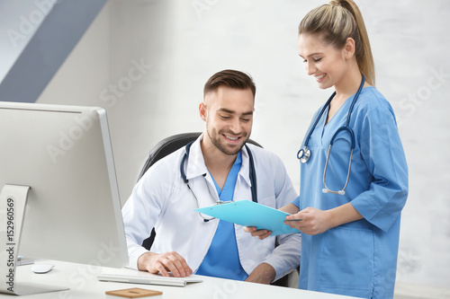 Doctor and medical assistant discussing issue in office Wallpaper Mural