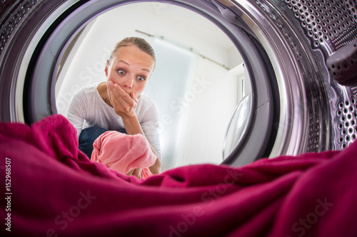 Young woman doing laundry - view from the washing machine Canvas Print