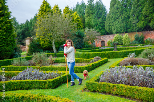 Fotografija  gardener woman stands amidst a maze of hedgerows in an English garden, leaning on a rake