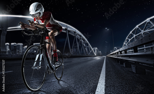 Photo sur Toile Cyclisme Sport backgrouns. Athletic woman cycling road bike in the evening. Dramatic view of the night city.