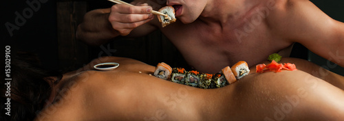Tuinposter Sushi bar Sexy couple. Japanese food restaurant, sushi maki roll plate, platter set. Hand take roll.