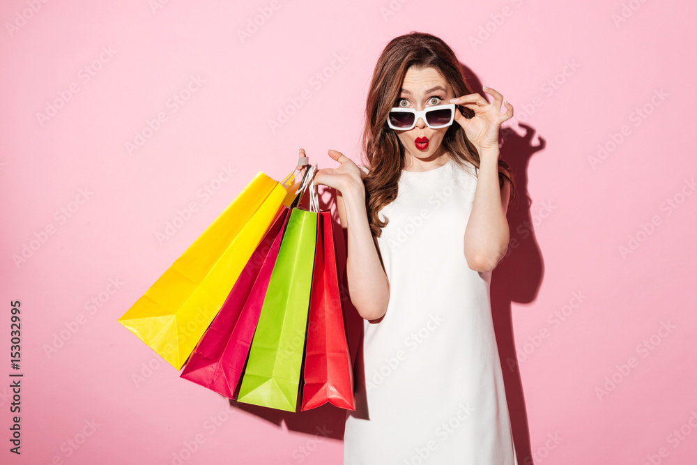 Fototapeta Shocked young brunette lady with shopping bags