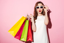 Shocked Young Brunette Woman With Shopping Bags