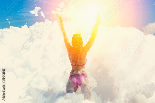 Photo Young woman dances and raised her hands at a foam party at the beach back view