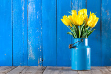 Bouquet Of Yellow Tulips In Vase On A Blue Background
