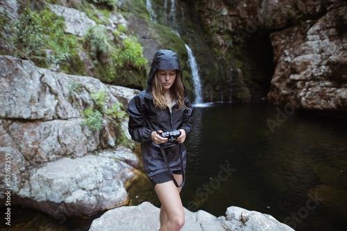 Woman holding a camera near waterfall