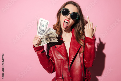 Fotografiet  Rude crazy girl in leather jacket holding money banknotes