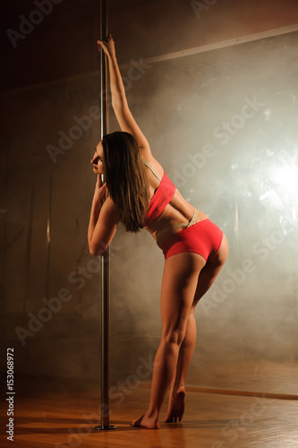 Obrazy na płótnie Canvas young hot woman in sexy lingerie performs sensual pole dance. Go-go dancer