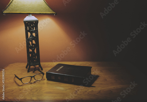Holy Bible Lying On A Wood Table With Glasses And Lamp Shining.