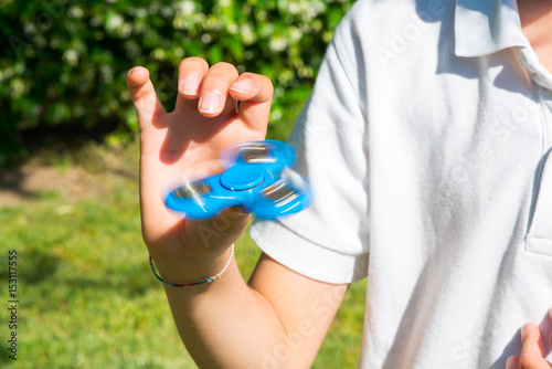 Fotografie, Obraz  Child playing with a blue fidget spinner