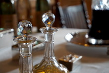 Old Glass Wine And Spirit Decanters On An Ornate Table In Natural Daylight