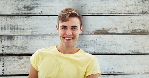 Portrait of man smiling over wooden wall