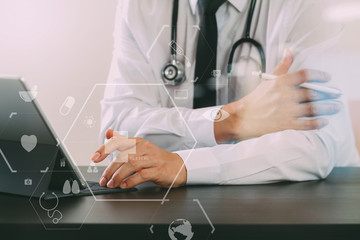 close up of smart medical doctor working with digital tablet computer and stylus pen and stethoscope on dark wooden desk with virtual icon diagram