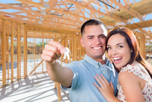 Young Military Couple On Site With House Keys Inside Their New Home Construction Framing.