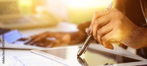 Tela Banner Dunkelhäutige Frau kalkuliert mit Stift auf Tablet im Gegenlichtt