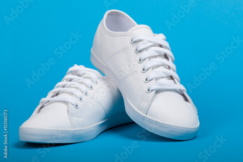 Fotografía  Pair of new white sneakers on blue background