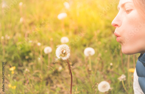 Keuken foto achterwand Lente Girl blowing white Dandelion in a field at sunset