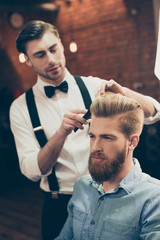 Panel Szklany Podświetlane Do fryzjera Barber shop classy dressed handsome stylist is doing a perfect hairstyle to a bearded guy in caual jeans outfit. Both concentrated and serious
